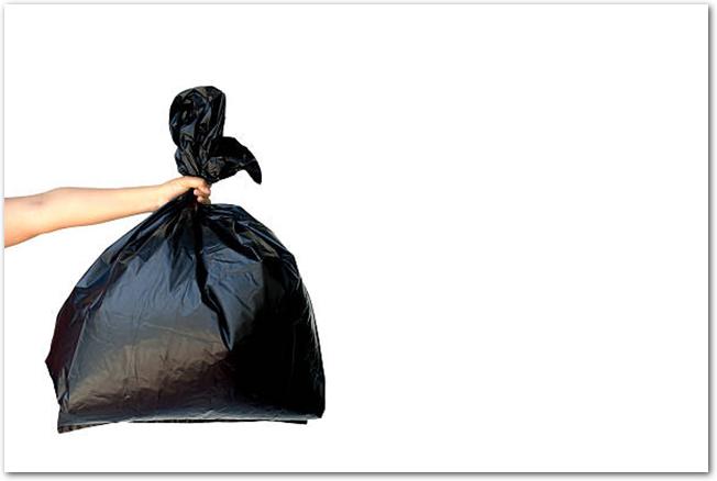 白い背景に黒いごみ袋を持った女性の手