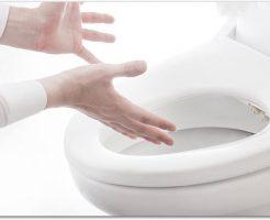 洋式トイレの便器にむかって手のひらを広げている様子